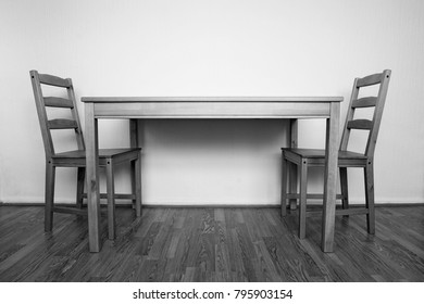Black an white photograph of simple interior with two wooden chairs and a table on wood block floor