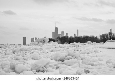 A black and white photograph of the skyline of Chicago from the harbor of Lake Michigan. Snow surrounds the foreground of the city after a blizzard.