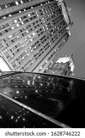 Black and white photograph of a skyscraper that is reflected in a car window.
