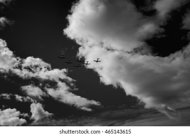 Black and white photograph of stunt planes flying in formation through dramatic clouds