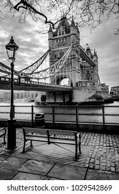 A black and white photograph of Tower Bridge in London with a park bench and cobblestone road in the forground
