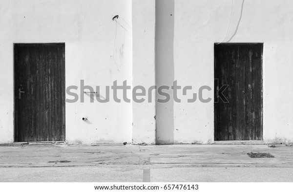 Black and white photograph of two doors in a white wall