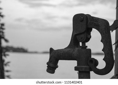 A black and white photograph of a water spigot with a ant on it back grounded by a calm lake.