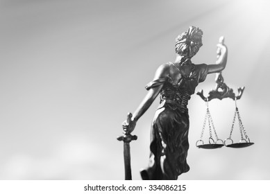 Black and white photography of back of sculpture of themis, femida or justice goddess on bright sky copyspace background