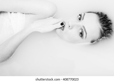 Black and white photography of beautiful tender young woman touching her lips with finger lying in the water on light background. Closeup portrait