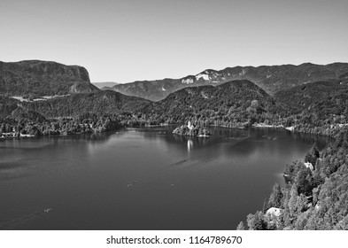 Black and white photography of Bled Island surrounded by the Bled Lake taken from the Bled Castle, Slovenia. The lake is located in the Julian Alps and is major tourist attraction of the country.