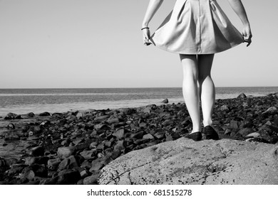 Black and white photography of girl standing on big stone by the ocean