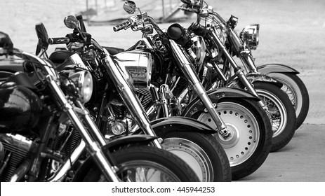 Black and white photography of group motorbikes parked together on outdoors background.