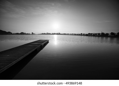 Black and white photography, pier at sunrise in a park of Manresa,Catalonia, Spain. Nice walking area with trees and water pond