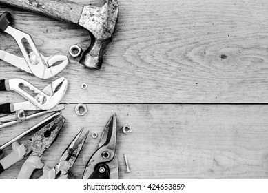 Black and white photography of toolkit with hammer, set of wrenches over wooden background copyspace