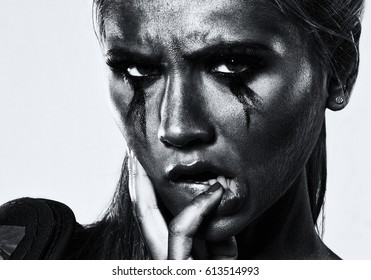 black and white photography of a Young beautiful girl with a crying make-up holds a  finger in her mouth