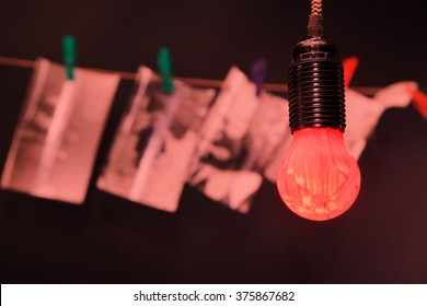 Black and white photos on a rope in the darkroom lit the red lamp