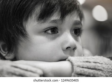 Black and white photos of upset little boy sitting alone,Kid sad face looking out, Unhappy child wearing knit jumper looking out with thinking face, Cropped shot bored child face, Spoiled children