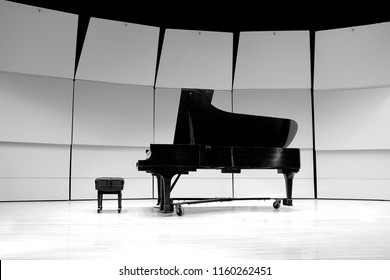 Black and white piano with bench on concert state for performance
