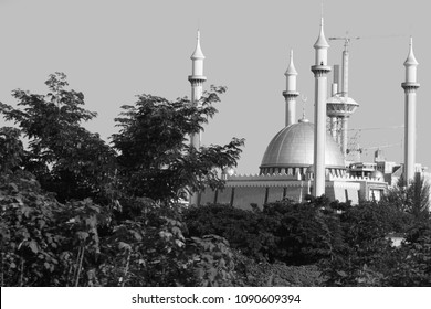 A black and white picture of the Abuja National Mosque in Abuja, Nigeria. It has 4 minarets and a big golden dome. It's in Nigeria capital and Islam is one of the religion.