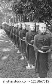 Black and white picture of aligned monks statues representing Offering at Kaw Ka Thaung Cave, located close to Hpa-An, Myanmar