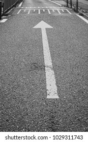 Black and white picture of anarrow on the road as marking