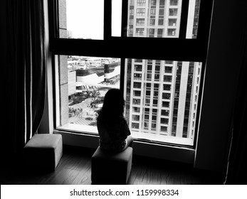 Black and white picture of backside of a kid sitting alone and looking outside through the window. Homesick or sadness or broken family concept