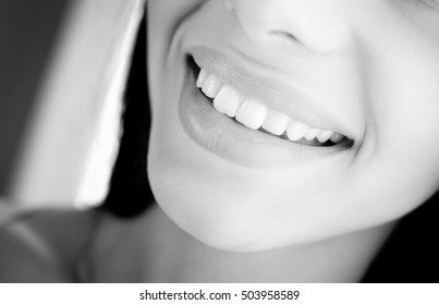 Black and white picture of beautiful happy smile. Closeup of teeth and natural lips on blurred indoor background.