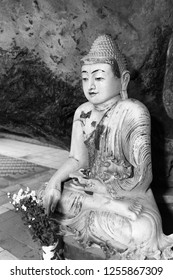 Black and white picture of Buddha statue sitting in meditation position  inside of Kaw Ka Thaung Cave, located close to Hpa-An, Myanmar