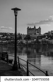 A black and white picture of the Castle of Saumur taken from the other side of the river.