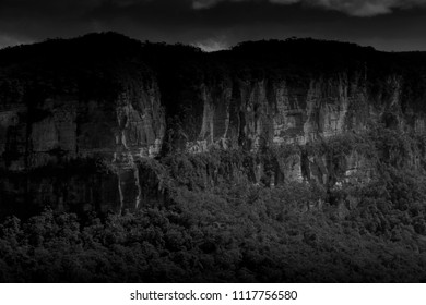 Black and White picture of a cliff face across a valley in the Blue Mountains