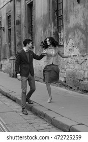 Black and white picture of a couple dancing on the old street