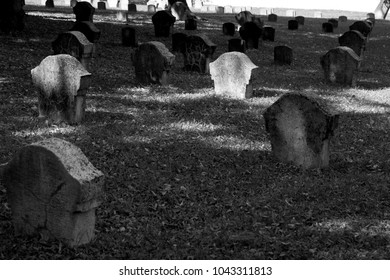 Black and white picture of a graveyard with the tombstones coming from the grass.