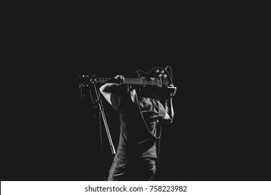 Black and white picture of guitarist playing solo as a rock star with the guitar on his shoulders