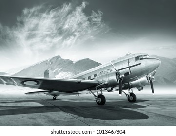 black and white picture of an historical aircraft on an airfield in the mountains