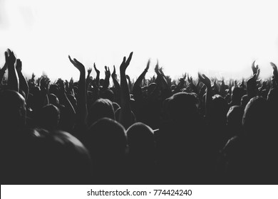 Black and white picture of huge crowd of people with the hands raised up on a big music show