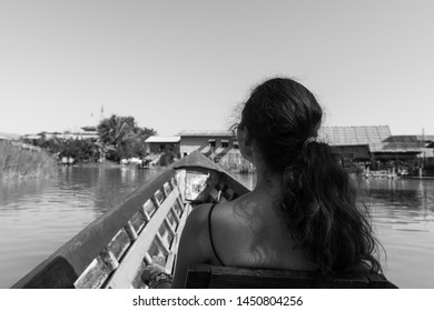 Black and white picture of long hair, brunette woman looking the beautiful village during boat trip in Inle Lake, Myanmar