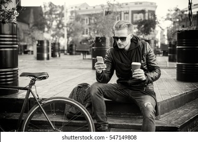 Black and white picture of man having coffee and using smartphone
