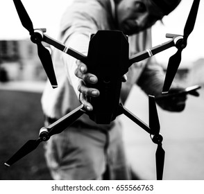 Black and white picture of a man holding a drone.