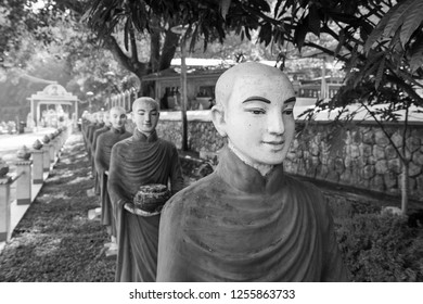 Black and white picture of many aligned monks statues at Kaw Ka Thaung Cave, located close to Hpa-An, Myanmar
