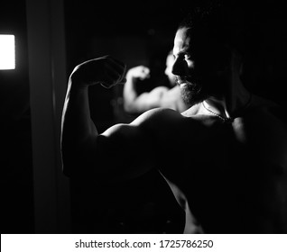 black and white picture of muscular young man in the dark, portrait of a young man in the dark