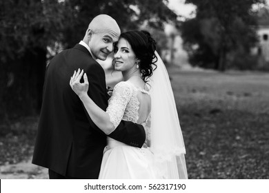 Black and white picture of newlyweds looking over their shoulders in park