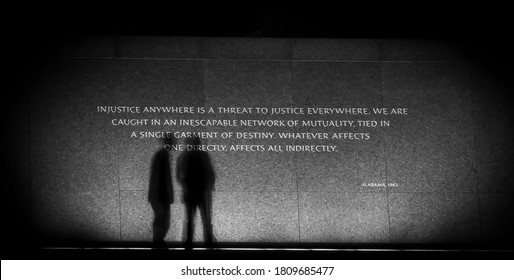 Black and white picture of a Reverend Martin Luther King Jr. Memorial quote in Washington, DC at night in July 2016 with the shadows of two people.