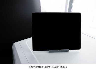 Black and white picture. Black screen tablet on white table