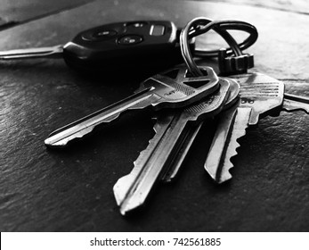 Black and white picture of a set of keys laying on top of a dark slate colored table.