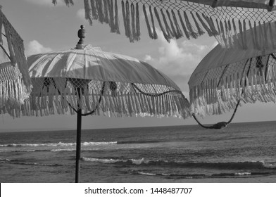 Black and white picture of some beautiful Balinese sun umbrella during sunset, decorated with yellow bulb lights and located at the famous Echo Beach in Canggu, Bali - Indonesia