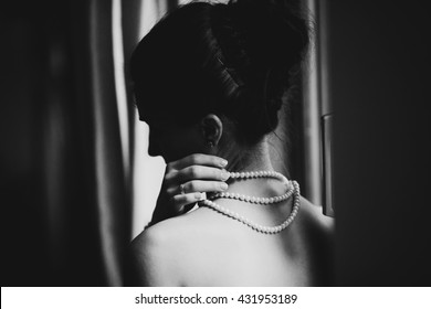 Black and white picture of a stunning lady touching her pearl necklace