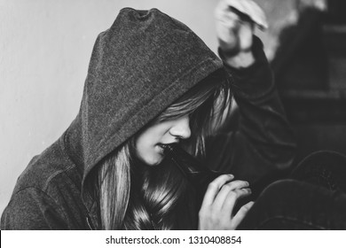 Black and white picture of teen girl drinking alcohol. Teenage alcoholism issue.
