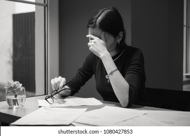 Black and white picture of an upset young woman with glasses sitting at the table with lots of documents