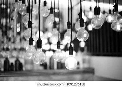 Black and white picture of vintage bulbs which are hanging on the ceiling.