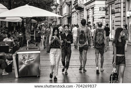 A Black And White Picture Of Walking Area In The City With People