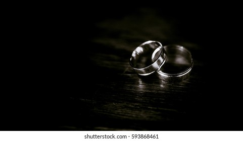 Black and white picture of wedding rings lying on dark wooden table