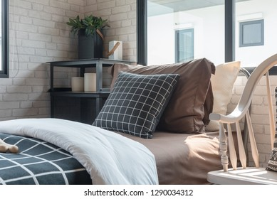 black and white pillows set on single bed in modern bedroom, interior decoration design concept