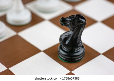 Black and white plastic chess pieces on a brown and white chess board with chess clock
