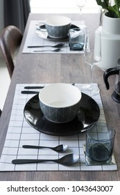 Black and white plate setting on wooden  dining table at home